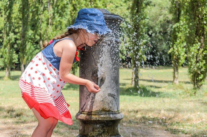 Wenig entzückendes Baby trinkt Wasser vom Trinkbrunnen der römischen Nase auf den Straßen von Rom lizenzfreie stockfotos