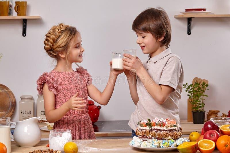 Wenig Freunde machen einen Kuchen zusammen an einer K?che gegen eine wei?e Wand mit Regalen auf ihm lizenzfreies stockbild