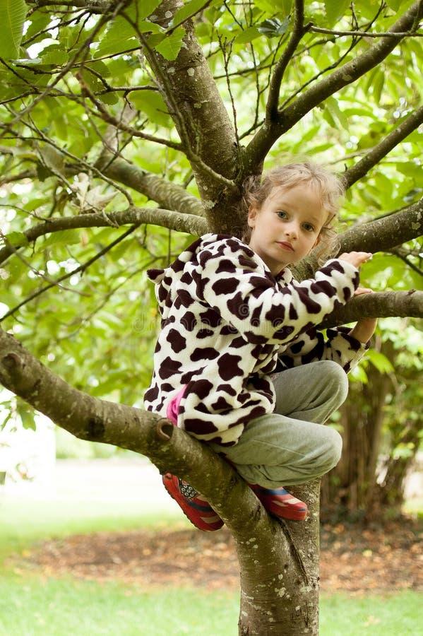 Wenig gelocktes Mädchen in einem beschmutzten Vlies und in Gummistiefeln sitzt auf einem Baum Ferien im Dorf, körperliche Tätigke stockbild