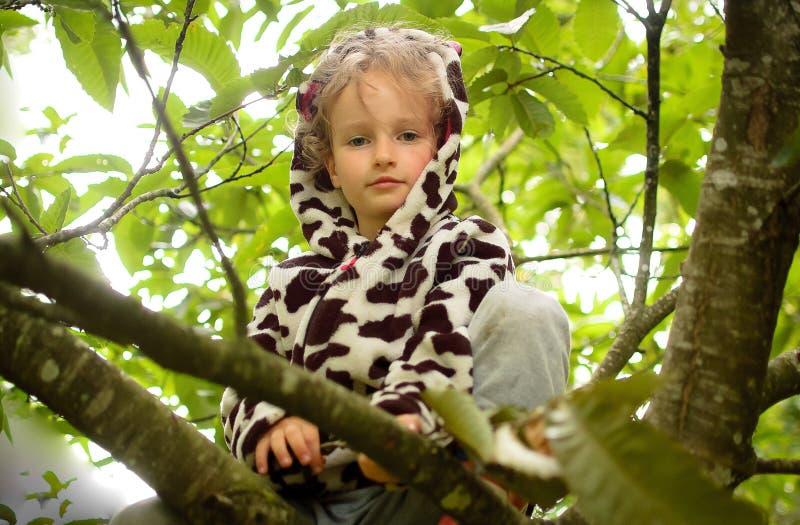 Wenig gelocktes Mädchen in einem beschmutzten Vlies und in Gummistiefeln sitzt auf einem Baum Ferien im Dorf, körperliche Tätigke stockfotos