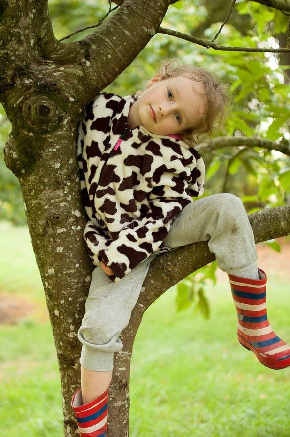 Wenig gelocktes Mädchen in einem beschmutzten Vlies und in Gummistiefeln sitzt auf einem Baum Ferien im Dorf, körperliche Tätigke lizenzfreie stockfotos
