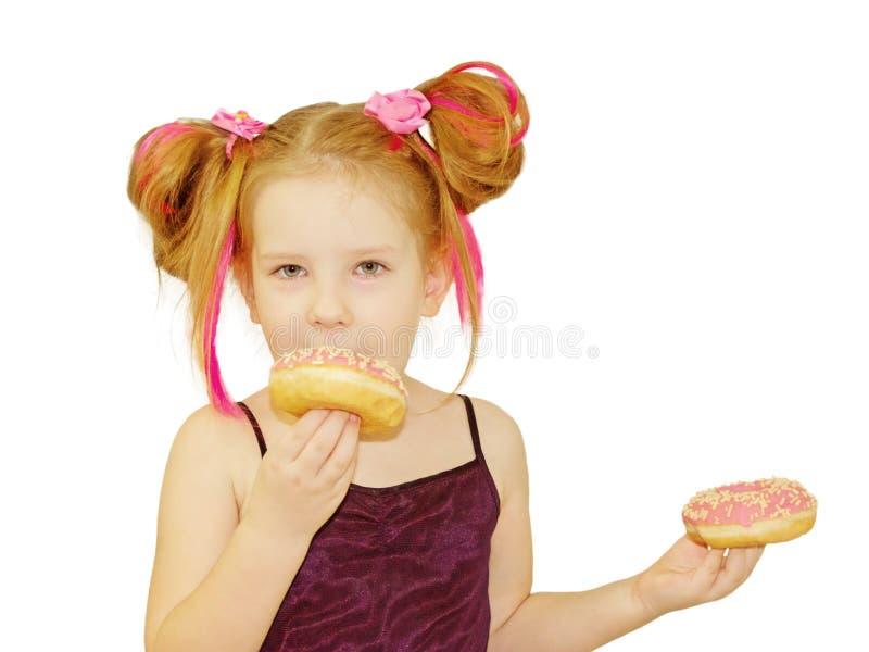 Wenig glückliches nettes Mädchen isst Donut auf weißer Hintergrundwand lizenzfreie stockbilder