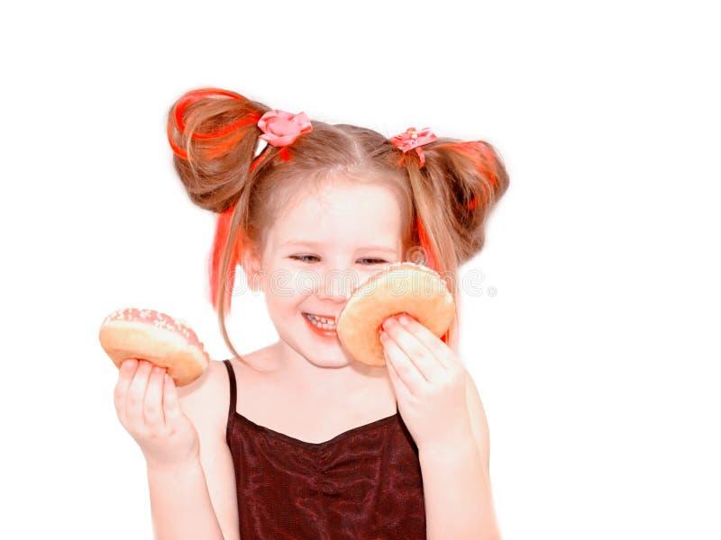 Wenig glückliches nettes Mädchen isst Donut auf weißer Hintergrundwand stockfotografie