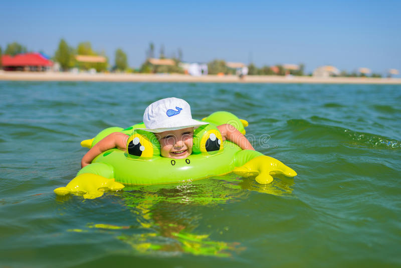Wenig glückliche Jungenschwimmen in Meer mit Gummiring stockbilder