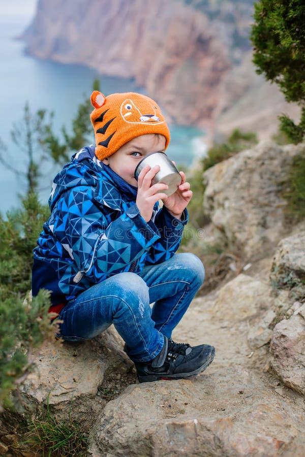Wenig glücklicher Junge trinkt von einer Thermosflasche lizenzfreie stockfotografie