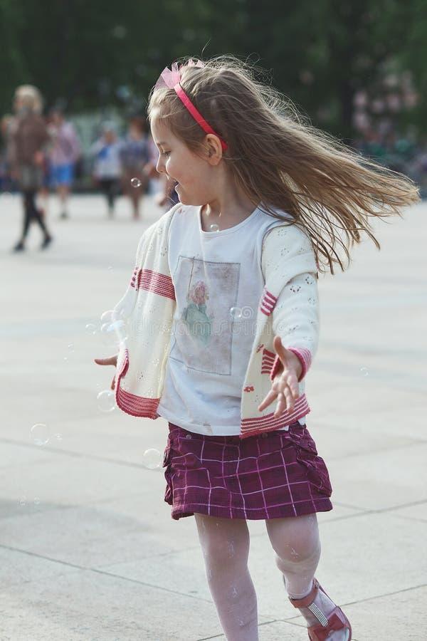 Wenig glückliches Mädchen, das mit den Seifenblasen in der Mitte der Stadt spielt lizenzfreies stockbild