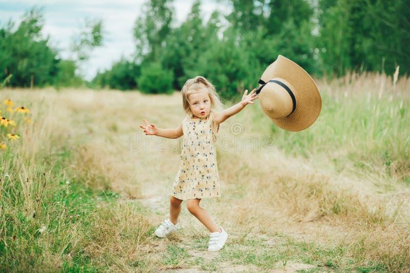 Wenig glückliches nettes Mädchen, das Spaß mit großem Hut auf der Natur spielt und hat lizenzfreie stockfotografie