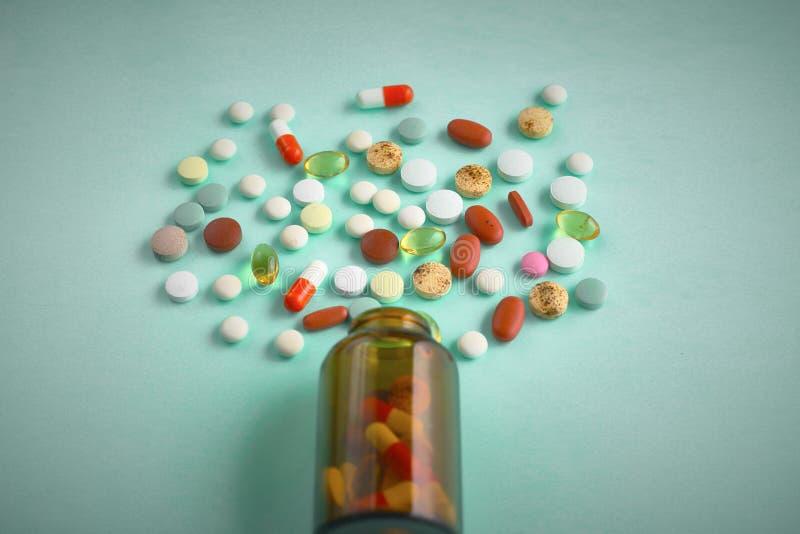 Wenig Glasflasche mit den Pillen versch?ttet ?ber einer Tabelle stockfoto