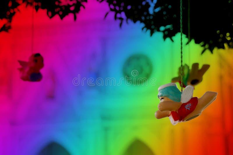 Wenig hängender beweglicher Engel auf buntem Hintergrund für reizenden Valentinsgruß lizenzfreie stockfotos