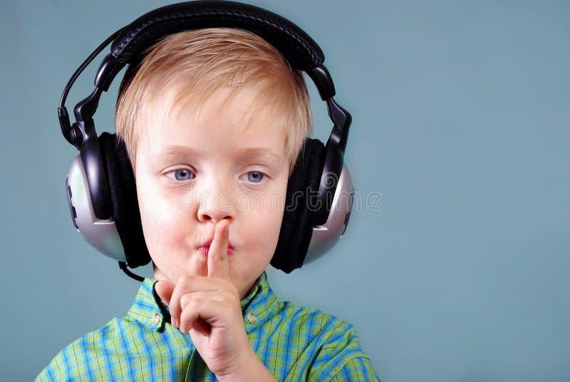 Wenig hörende Musik des Jungen auf Kopfhörern Zeichen ruhiger lizenzfreie stockbilder