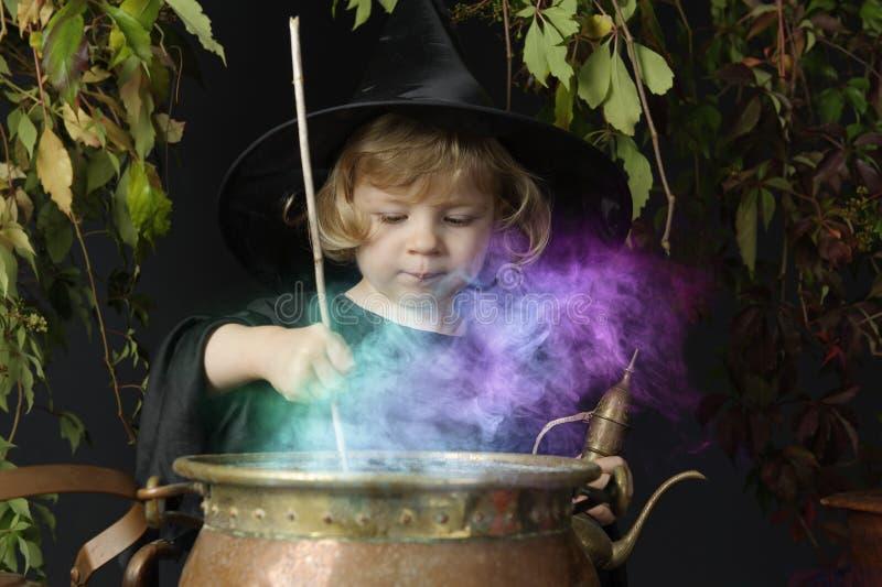 Wenig Halloween-Hexe mit großem Kessel lizenzfreies stockbild