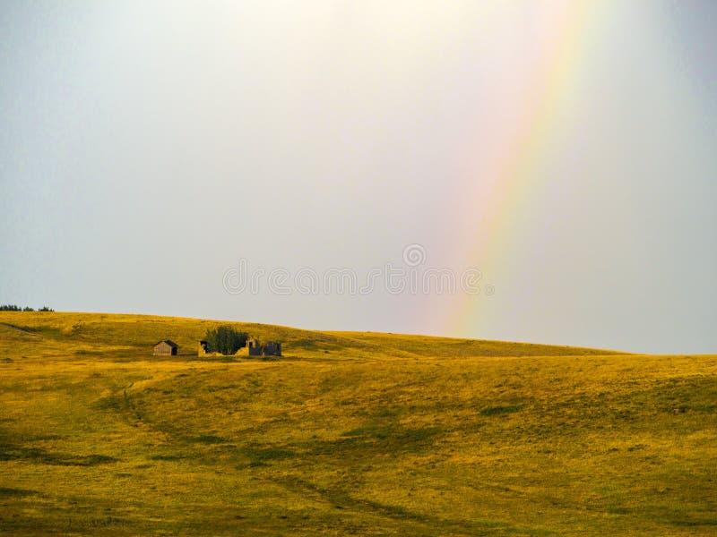 Wenig Haus auf dem Grasland mit geringfügigen Hügeln und ein schwacher Regenbogen im Hintergrund lizenzfreie stockbilder