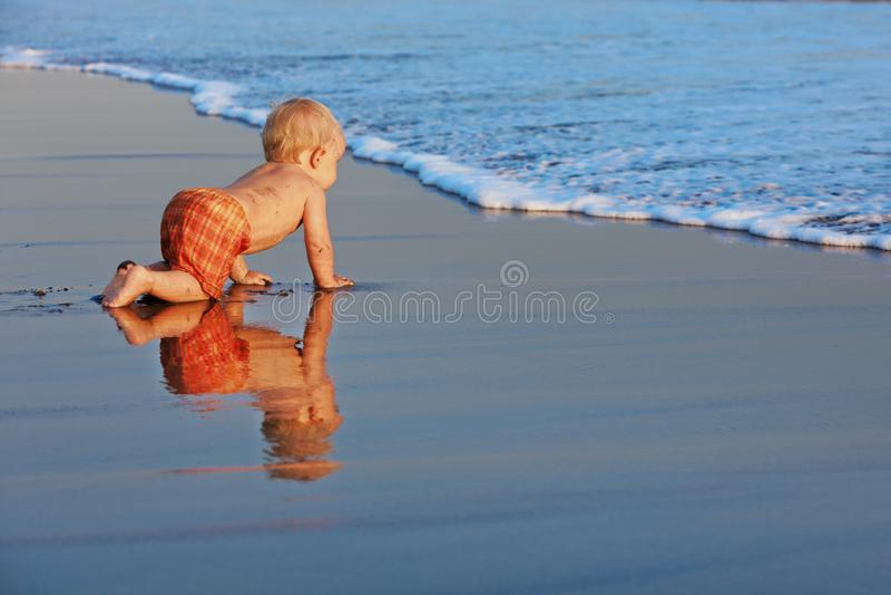 Wenig Junge auf Sonnenuntergangseestrand lizenzfreie stockfotografie
