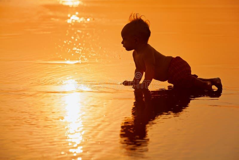 Wenig Junge auf Sonnenuntergangseestrand stockfoto