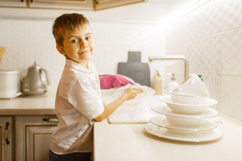 Wenig Junge in den Handschuhen, die Teller auf der Küche waschen stockbilder