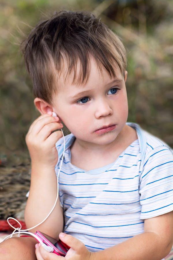 Wenig Junge in den Kopfhörern draußen stockbilder