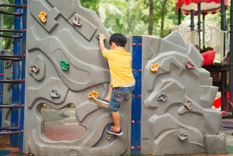 Wenig Junge, der auf der Felsenwand am Spielplatz klettert lizenzfreie stockfotos