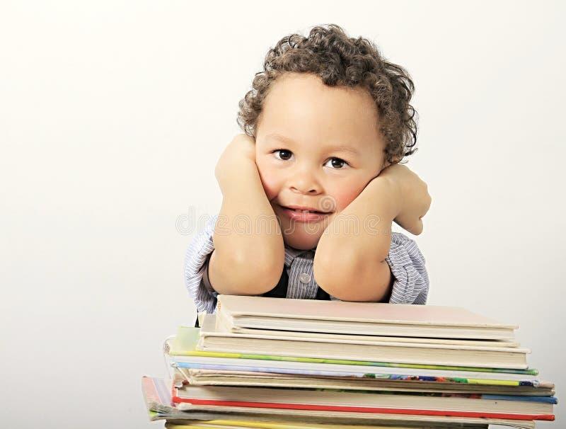 Wenig Junge, der auf seinen Schulbüchern sich lehnt stockfoto