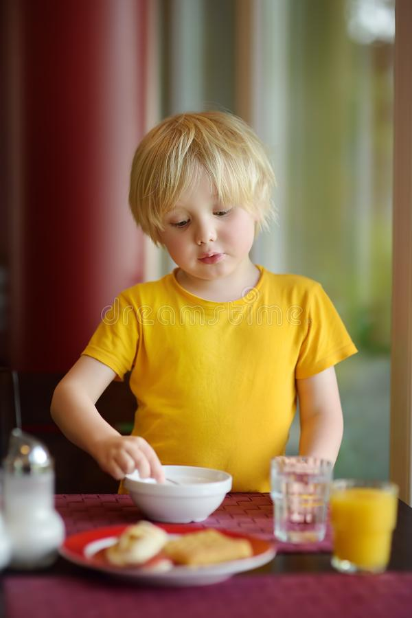 Wenig Junge, der gesundes Frühstück im Hotelrestaurant isst Geschmackvolle Mahlzeit im Haus lizenzfreie stockbilder