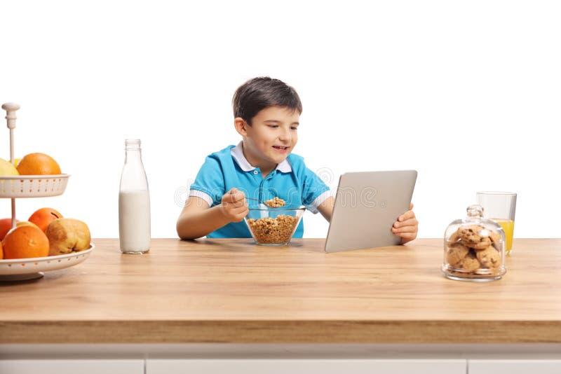 Wenig Junge, der Getreide für brekfast an einem hölzernen Zähler isst und in eine Tablette aufpasst stockbilder