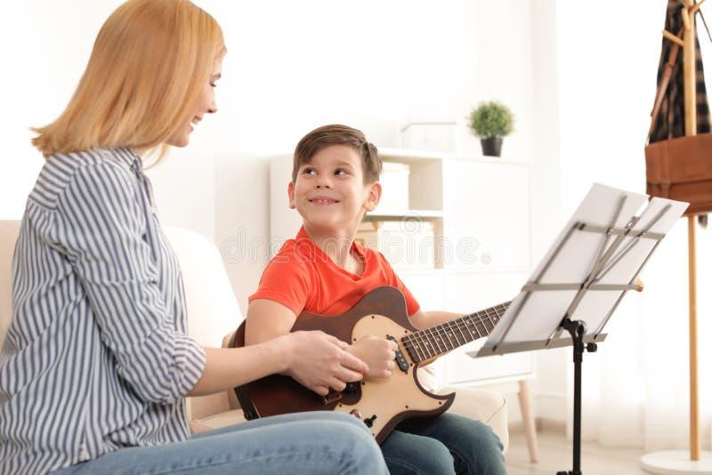 Wenig Junge, der Gitarre mit seinem Lehrer spielt Lernen der Anmerkungen stockfoto