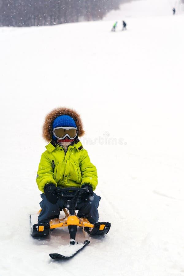 Wenig Junge, der hinunter einen Hügel im Winter rodelt Kind in den Schutzbrillen auf einem Schlitten Spaß im Freien für Familie U lizenzfreie stockfotos