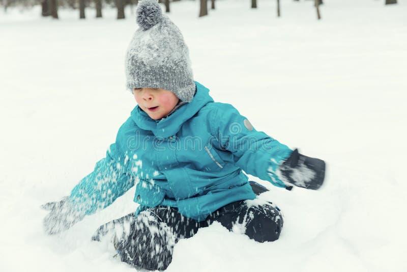 Wenig Junge, der im Schnee und im Lachen spielt lizenzfreie stockfotografie