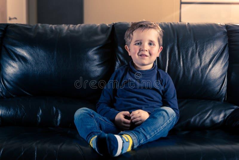 Wenig Junge, der im schwarzen Sofa sitzt lizenzfreie stockfotografie
