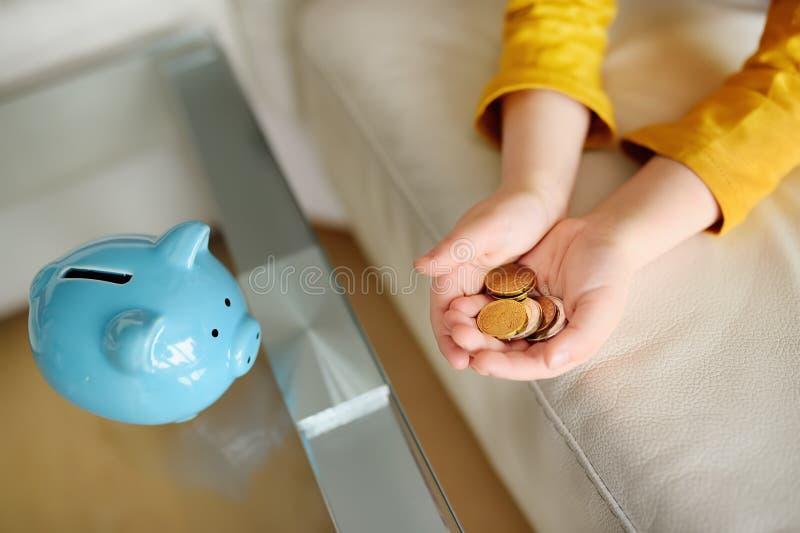 Wenig Junge, der mit Münzen und Träumen spielt von, was er kaufen kann Ausbildung von Kindern in der Finanzbildung stockfoto