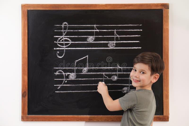 Wenig Junge, der Musikanmerkungen auf Tafel schreibt stockfoto