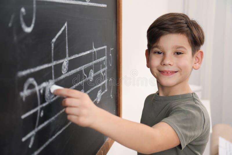 Wenig Junge, der Musikanmerkungen auf Tafel schreibt stockbilder