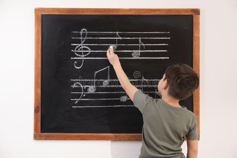 Wenig Junge, der Musikanmerkungen auf Tafel schreibt lizenzfreie stockbilder
