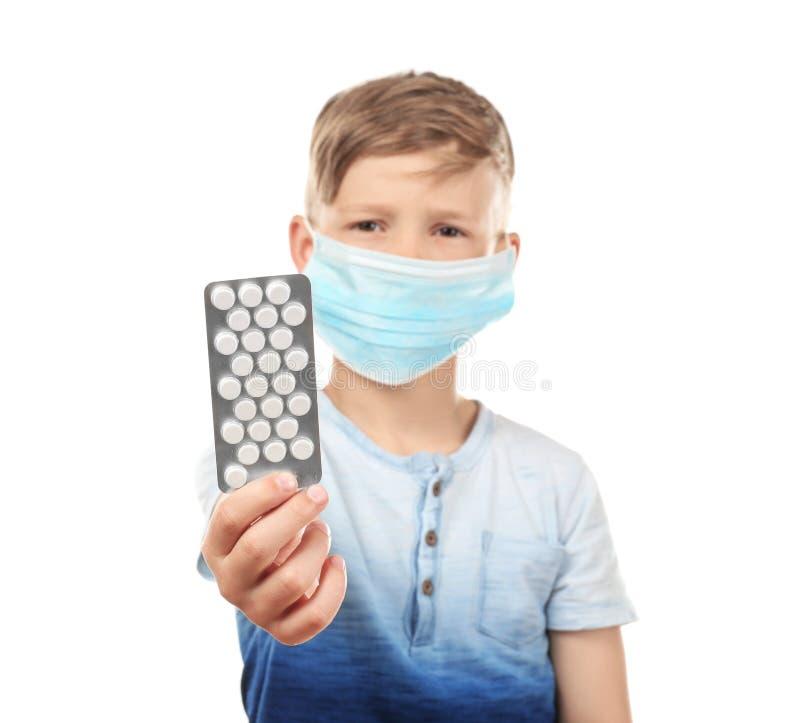 Wenig Junge in der Schutzmaske, die Pillen auf weißem Hintergrund hält Allergiekonzept lizenzfreie stockbilder
