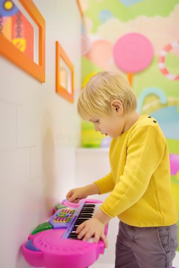 Wenig Junge, der Spaß in der Unterhaltung in der Spielmitte hat Baby, das auf einem Spielzeugklavier am Spielzimmer der Kinderkin stockfotos