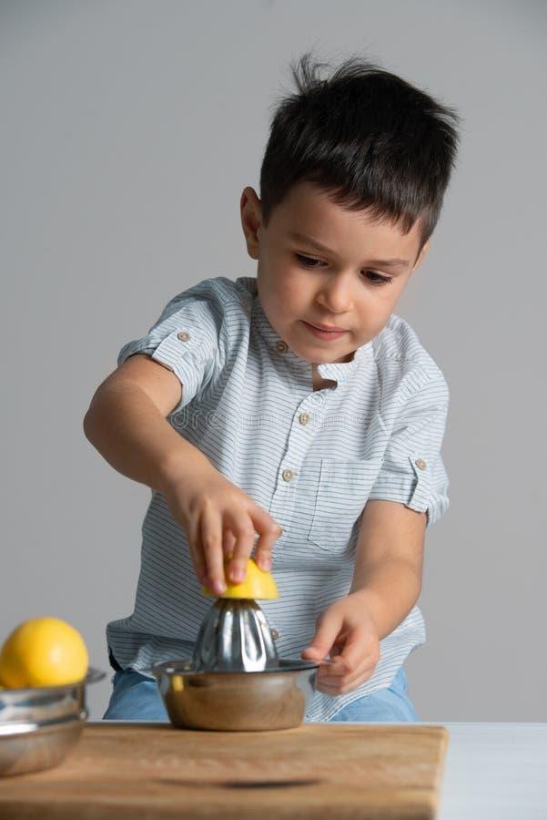Wenig Junge in einem blauen T-Shirt, das Limonade macht lizenzfreies stockfoto