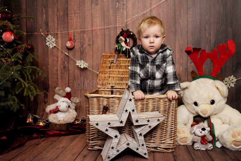 Wenig Junge in einer Weihnachtsatmosphäre stockfotografie