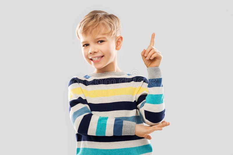 Wenig Junge in gestreiftem Pullover Finger oben zeigend stockfotografie