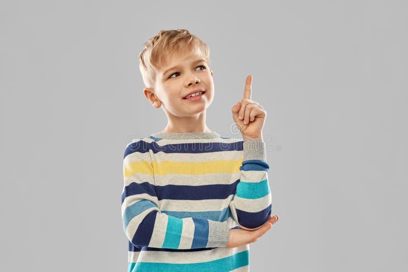 Wenig Junge in gestreiftem Pullover Finger oben zeigend stockbild