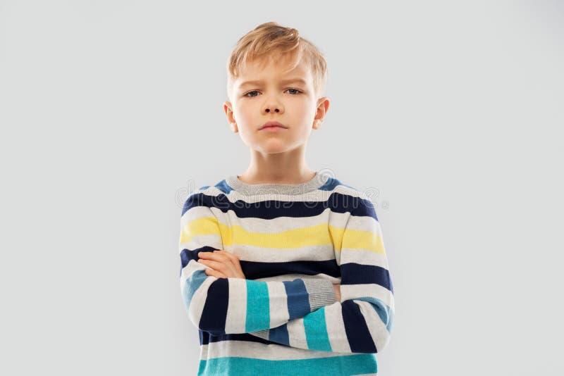 Wenig Junge in gestreiftem Pullover mit den gekreuzten Armen stockfotos