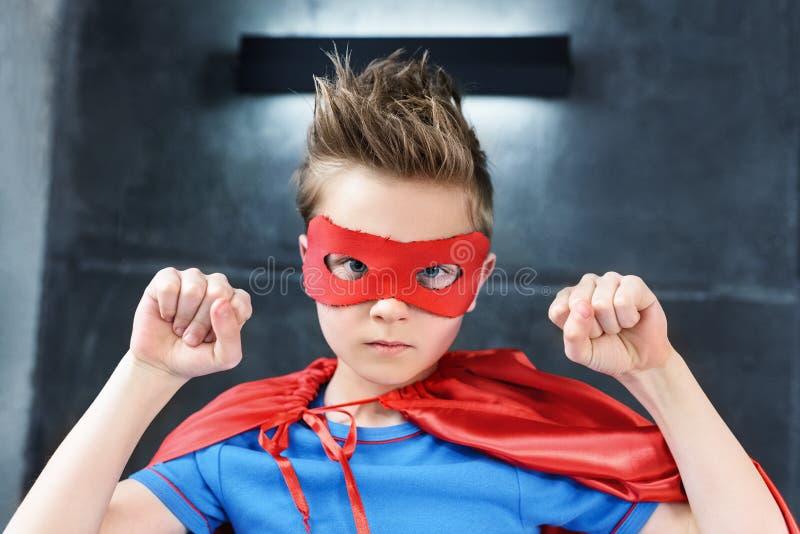 wenig Junge im roten Superheldkostüm gestikulierend und schauend stockfotografie