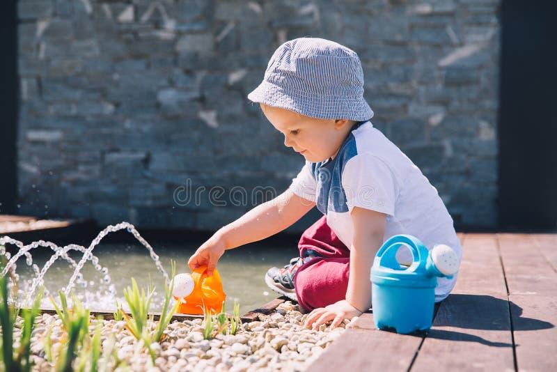 Wenig Junge im schönen Zengarten nahe Brunnen lizenzfreie stockbilder