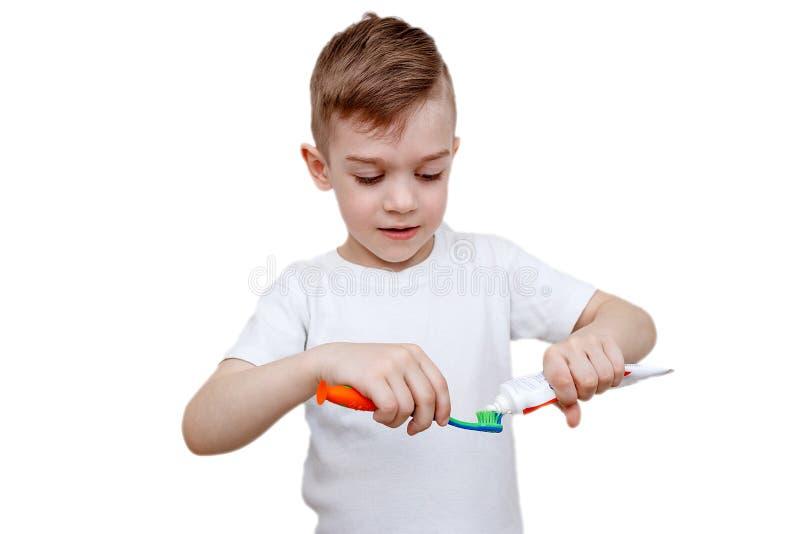 Wenig Junge im weißen T-Shirt drückt Zahnpasta auf Bürste zusammen Gesundheitswesen-, Hygiene- und Kindheitskonzept Kariesverhind stockfotografie