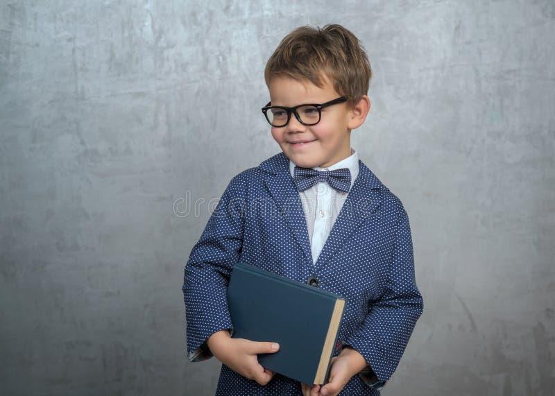 Wenig Junge mit Gläsern und einem Buch auf einem grauen Hintergrund lizenzfreie stockfotografie