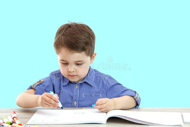 Wenig Junge sitzt und zeichnet schreibt auf einen lokalisierten Hintergrund lizenzfreie stockbilder