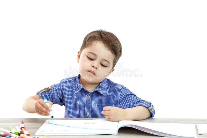 Wenig Junge sitzt und zeichnet schreibt auf einen lokalisierten Hintergrund lizenzfreies stockfoto