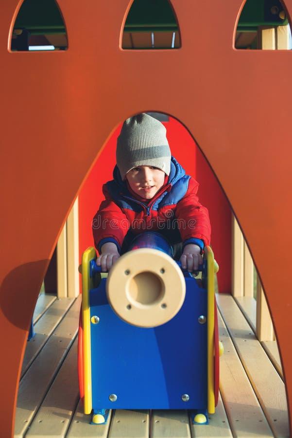 Wenig Junge spielt am modernen Stadtspielplatz am kalten Tag Glückliche Kindheit Moderne Kinderbunter Spielplatz Kindart und weis lizenzfreies stockfoto