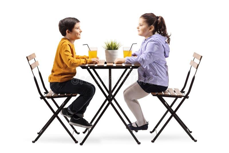 Wenig Junge und Mädchen, die an einem Tisch mit einem Orangensaft sitzen stockfotos
