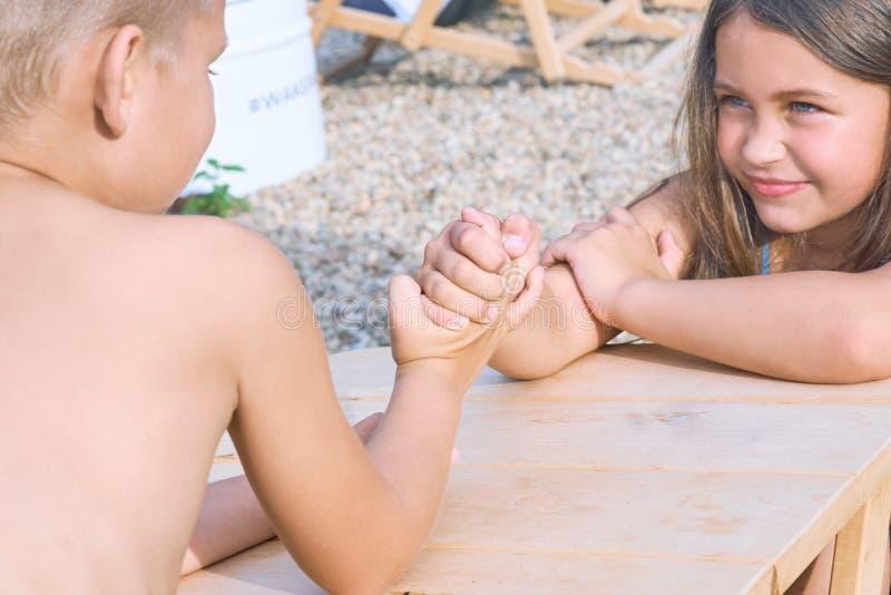 Wenig Junge und Mädchen, die bei Tisch am Sommerstrand und -Armdrücken sitzen Lustige Spiele für Sommerferien lizenzfreie stockfotografie
