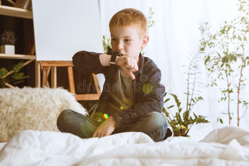 Wenig Junge unter Verwendung der verschiedenen Geräte zu Hause lizenzfreie stockbilder