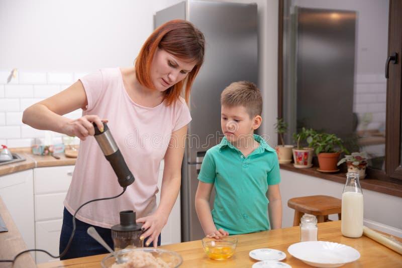 Wenig Junge, welche seiner Mutter mit dem Kochen in der Küche hilft stockbilder